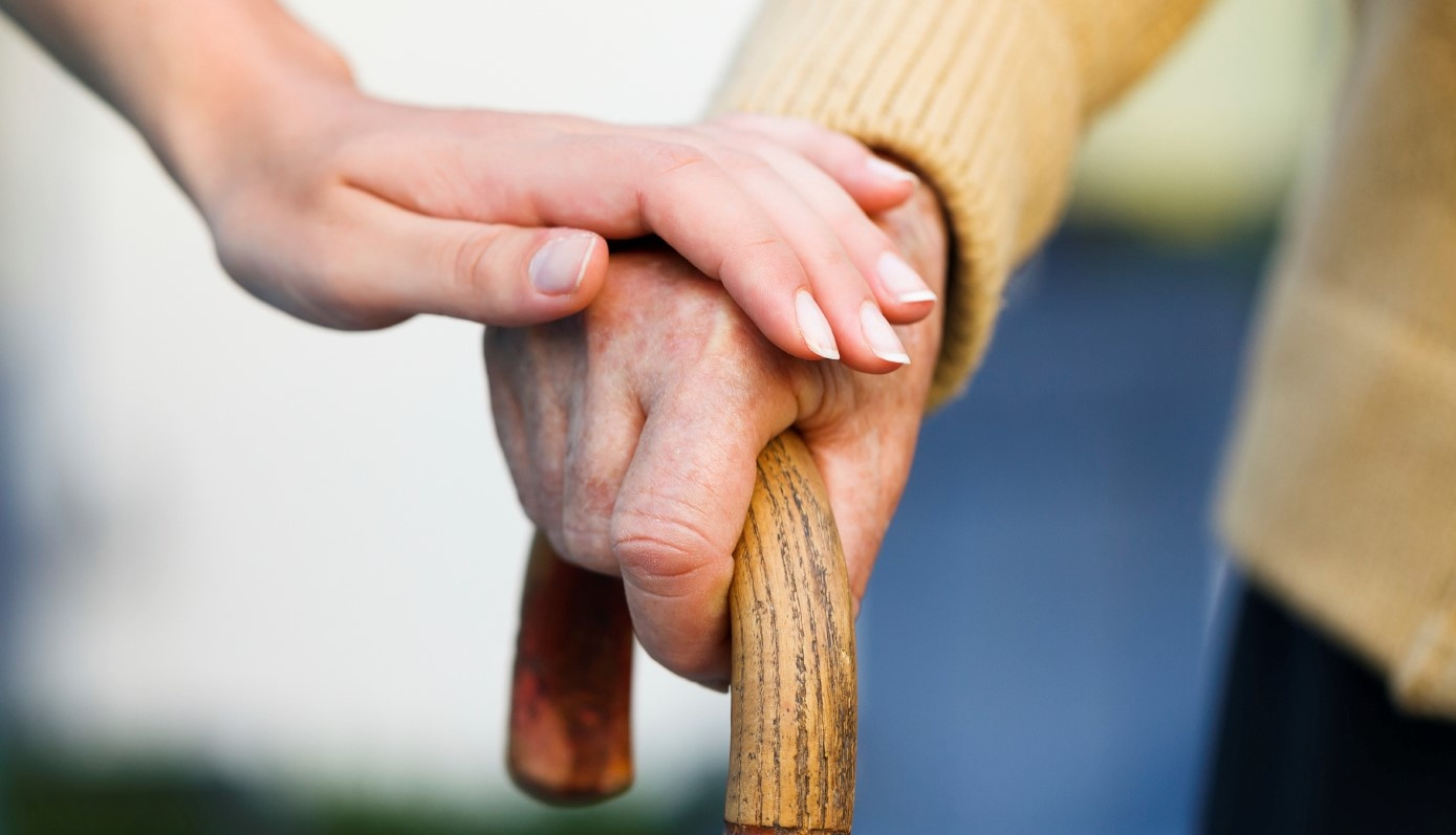 Senior Living - Nurse holding a patients hand